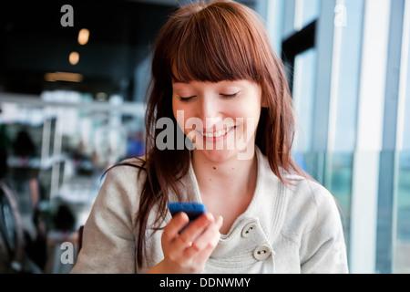 Femme textos sur téléphone mobile et souriant, assis dans un café