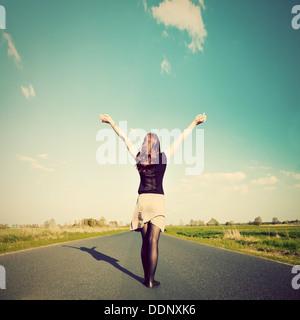 Happy woman standing with hands up sur route droite face à soleil. Avenir / liberté / espoir / concept de réussite Banque D'Images