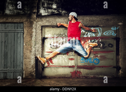 Jeune homme / DANSE / saut de l'adolescence sur graffiti grunge wall background Banque D'Images
