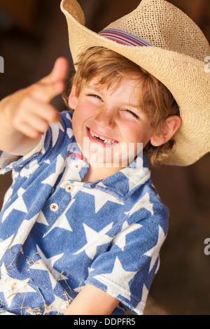 Young happy smiling blonde boy enfant portant une étoile bleue chemise et chapeau de cowboy assis sur des bottes Banque D'Images