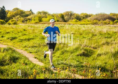 Un jeune homme le jogging dans le parc de découverte, Seattle, Washington. Banque D'Images