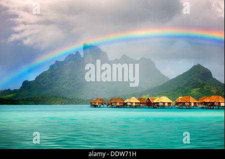 Bungalows sur l'eau avec rainbow et Mt. Otemanu. Bora Bora. Polynésie Française Banque D'Images