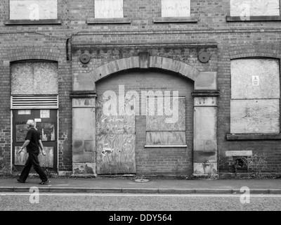 Homme marchant à travers l'armature devant une vieille usine abandonnée et abandonnés avec barricadèrent windows. Banque D'Images