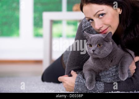 Une jeune femme à la maison avec un chat British Shorthair Banque D'Images