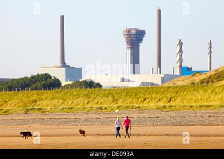 Centrale nucléaire de Sellafield avec un couple promènent leurs chiens sur le bord de la mer en face de Cumbria Banque D'Images