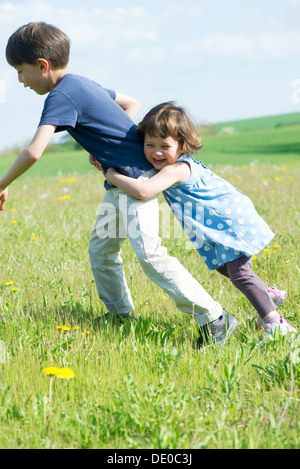 Les jeunes frères et sœurs à jouer ensemble à l'extérieur Banque D'Images