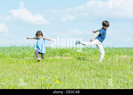 Les enfants courent sur le terrain avec le bras Banque D'Images