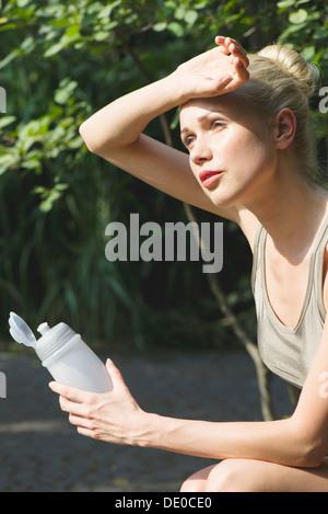 Jeune femme assise à l'extérieur avec une bouteille d'eau, l'essuyant le front avec le dos de la main Banque D'Images
