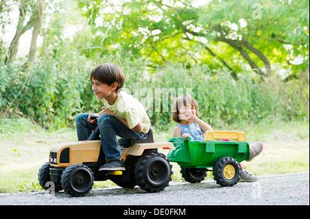 Les jeunes frère et sœur équitation sur tracteur jouet Banque D'Images
