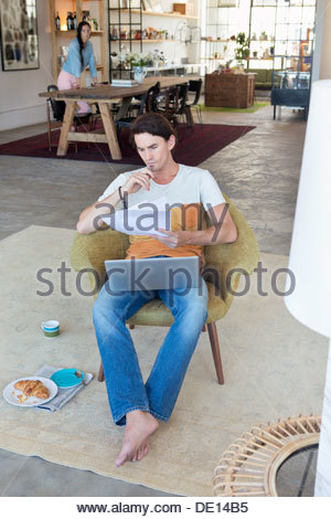 Serious man looking down at paperwork and laptop in livingroom Banque D'Images