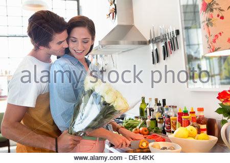 Female friends en cuisine avec bouquet de fleurs Banque D'Images
