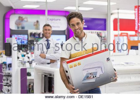 Portrait of smiling man holding zone imprimante dans votre magasin d'électronique Banque D'Images