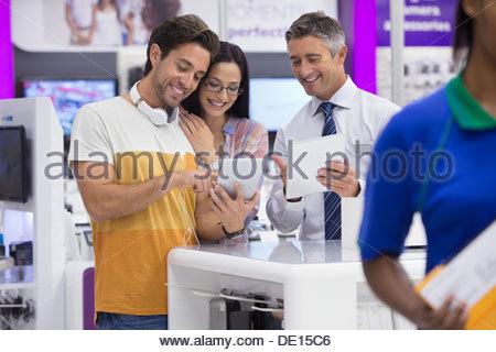 Vendeur montrant deux comprimés en magasin d'électronique numérique Banque D'Images