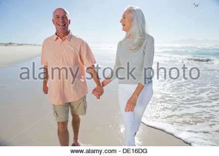Happy senior couple holding hands and walking on sunny beach Banque D'Images