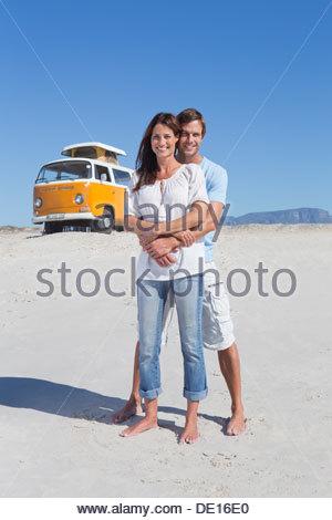 Portrait of happy couple hugging on beach avec van en arrière-plan Banque D'Images