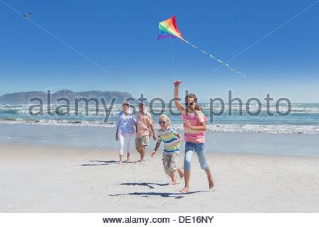 L'observation des grands-parents petits-enfants jouer avec kite on sunny beach Banque D'Images
