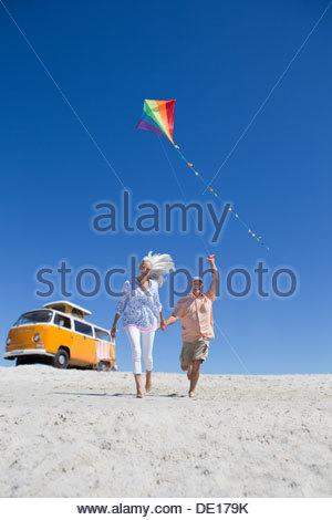 Happy senior avec cerf-volant sur la plage ensoleillée avec van en arrière-plan Banque D'Images