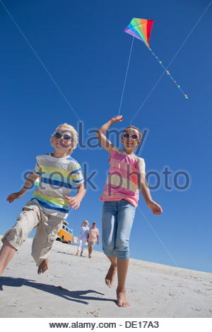 Garçon et fille avec kite s'exécutant sur sunny beach Banque D'Images
