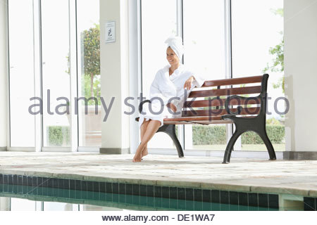 Portrait of smiling woman in bathrobe sitting on bench poolside at spa Banque D'Images