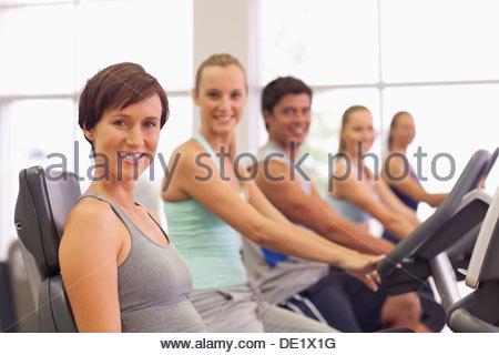 Portrait of smiling people sur des vélos d'exercice dans un gymnase Banque D'Images