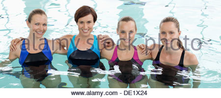 Portrait of smiling women in a row in swimming pool Banque D'Images