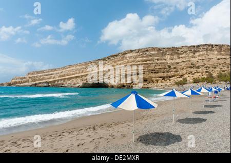 Grotte néolithique habitations dans le grès jaune, des parasols sur la plage de Matala, ancien site de l'hippies, Banque D'Images