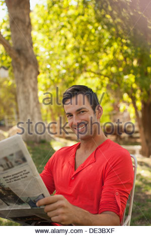 Man reading newspaper outdoors Banque D'Images