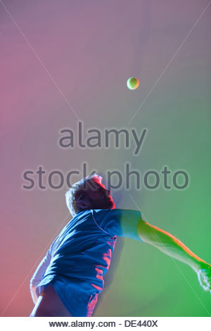 Tennis player swinging racket Banque D'Images