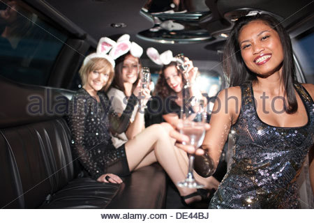 Woman drinking champagne in limo Banque D'Images