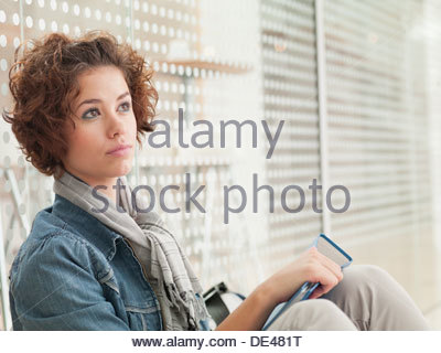 Pensive woman holding book Banque D'Images