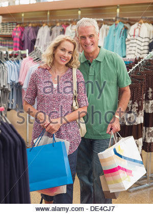 Couple carrying shopping bags in store Banque D'Images