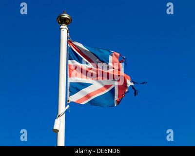 La déchiré Union Jack flag sur un mât avec ciel bleu derrière Banque D'Images