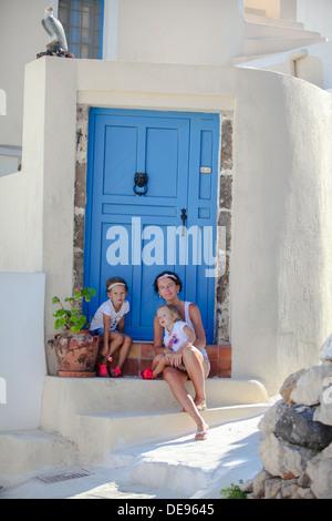 Jeune mère et sa fille assis sur porte ancienne maison street Emporio, Santorini Banque D'Images