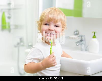 Happy kid ou l'enfant se brosser les dents dans la salle de bains. L'hygiène dentaire. Banque D'Images