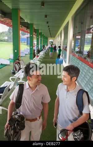 Deux amis de sourire et de se préparer à quitter le terrain de golf Banque D'Images