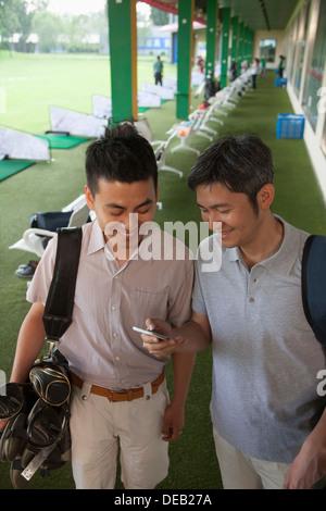 Deux amis de sourire et de se préparer à quitter le terrain de golf en regardant le téléphone Banque D'Images