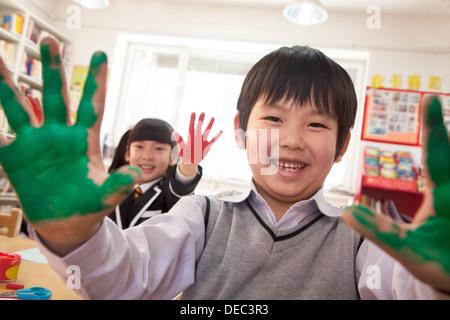 Les enfants de l'école montrant leurs mains couvertes de peinture Banque D'Images