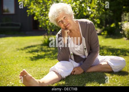 Ambiance vieille femme assis sur l'herbe avec sa main sur Menton vous regarde. Senior woman sitting in backyard Banque D'Images