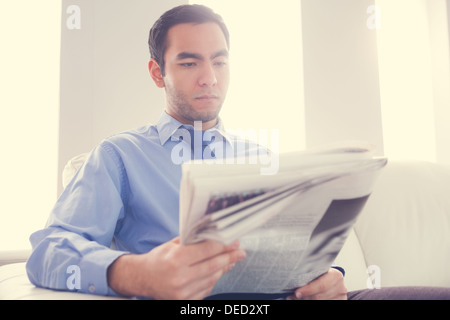 Handsome businessman reading newspaper