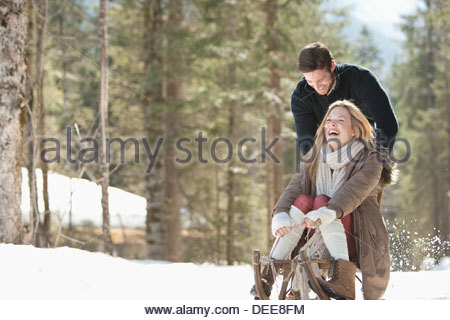 Man pushing woman on sled in Snowy Woods Banque D'Images