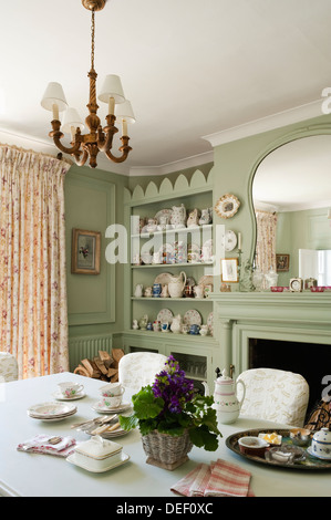 Country house salle à manger avec pottert collection sur des étagères encastrées peint en vert pastel Banque D'Images