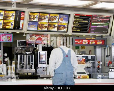 McDonald's le compteur avec un homme à la recherche, à l'aide du menu Banque D'Images