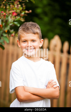 Boy crossing arms and smiling Banque D'Images