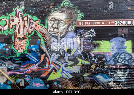 L'Art de rue sur un mur de Toronto - Musician playing air guitar Banque D'Images