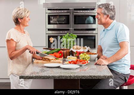 Man & woman couple préparation des sandwichs sains à la maison cuisine avec jambon, fromage, salade de laitue et Banque D'Images