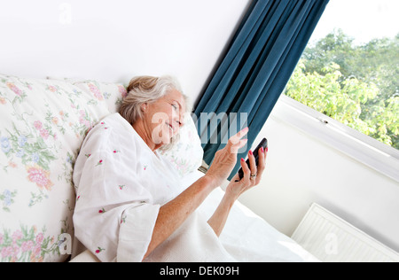 Happy senior woman using cell phone bed accueil Banque D'Images