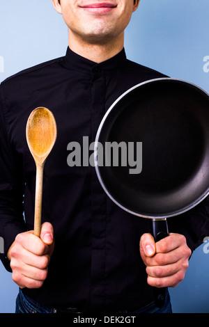 Jeune Cuisinier tenant une poêle et une cuillère en bois Banque D'Images