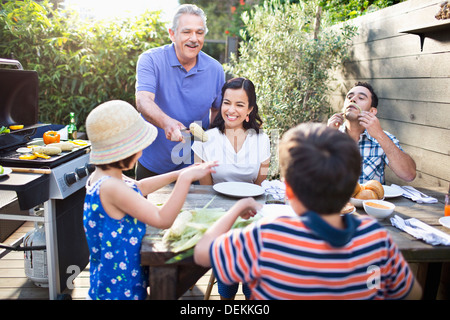Family eating at table outdoors Banque D'Images