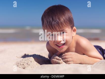 Portrait of a cute heureux enfant jouant dans le sable sur la plage. Le lac Huron, en Ontario, Canada. Banque D'Images