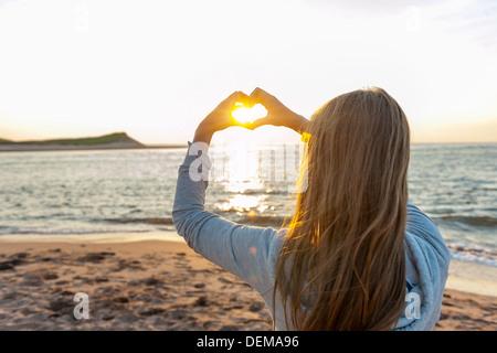 Jeune fille blonde holding hands in heart shape ossature bois coucher de soleil au coucher du soleil sur l'ocean Banque D'Images
